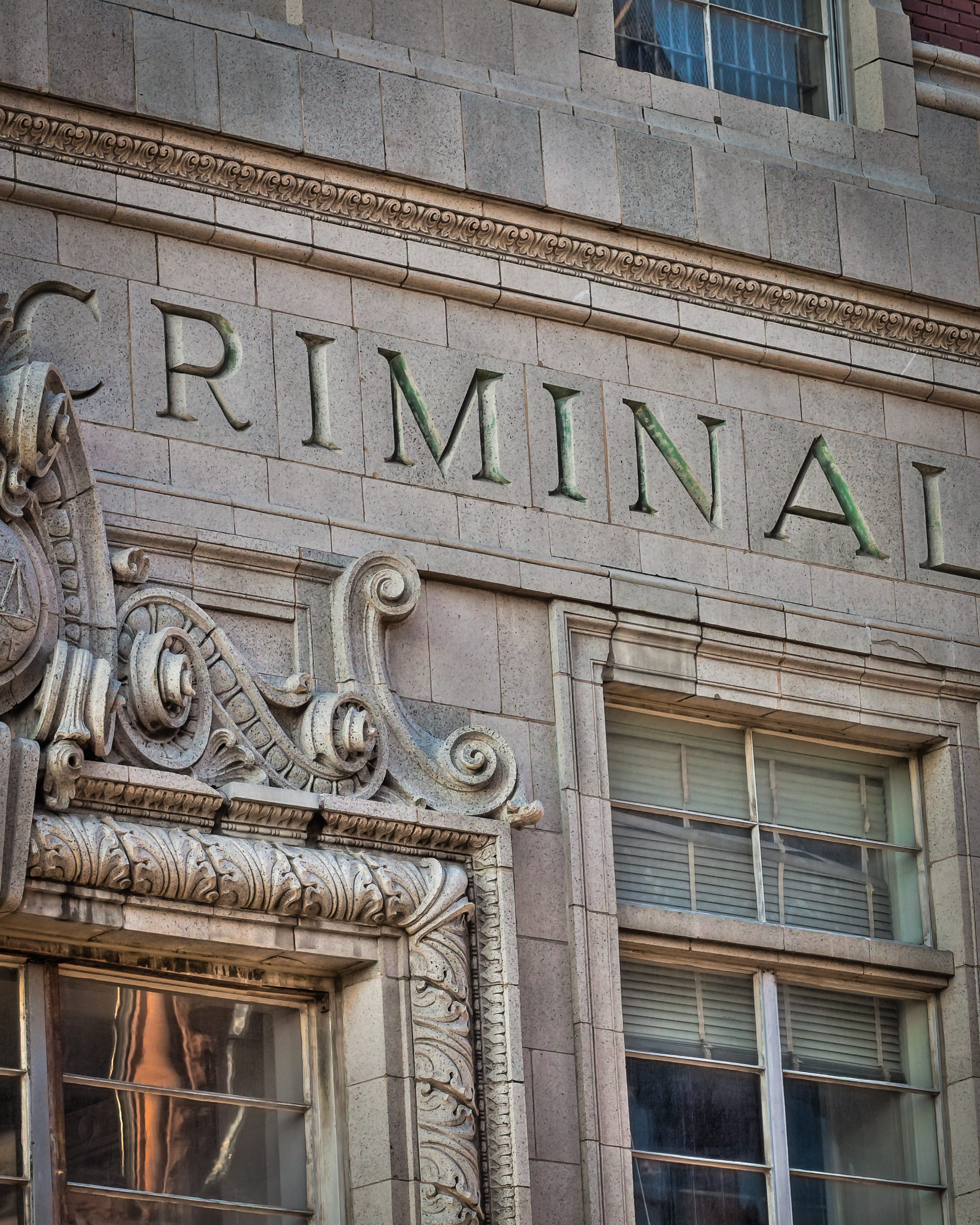 "Building photo showing the word ""Criminal"" carved into marble"